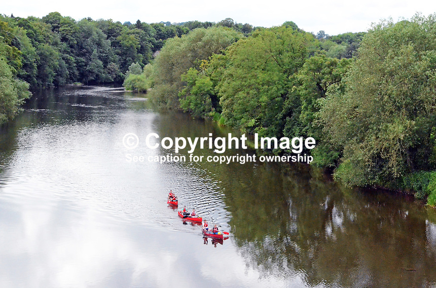 Canoeists on tree-lined River Wye at Hay-on-Wye, Herefordshire, UK, July 2014, 201407053261. <br />