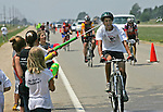 A rider gets a shot in the ear as children from Waukee, Iowa, try to cool off bikers finishing their fourth day of RAGBRAI, an annual bike ride across the state of Iowa that draws bike enthusiasts from all over the world.