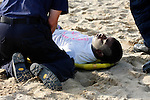 EMTs helping an African American teenager hurt on a beach