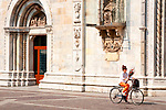 A woman holding a bunch of flowers, rides her bike past the Cathedarl in Como, Italy.