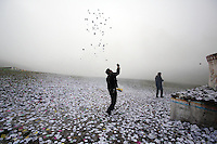"A Tibetan man throws small pieces of paper, called ""wind horses,"" into the air, next to a stupa on top of a mountain on the Tibetan Plateau. This practice is is said to bring good luck and a safe journey."