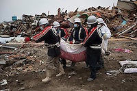 Rescue workers carry a body wrapped in blankets. Thousands of people died in this small town which ran out of body bags. On 11 March 2011 a magnitude 9 earthquake struck 130 km off the coast of Northern Japan causing a massive Tsunami that swept across the coast of Northern Honshu. The earthquake and tsunami caused extensive damage and loss of life.