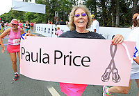 A runner crosses the finish line holding a sign during the 32nd annual Charlottesville Women's Four Miler race Saturday in Charlottesville, VA. Photo/The Daily Progress/Andrew Shurtleff