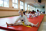 Albany, CA Boy, six-years-old, doing warm-up exercises before class's Tae Quan Do demonstration  MR