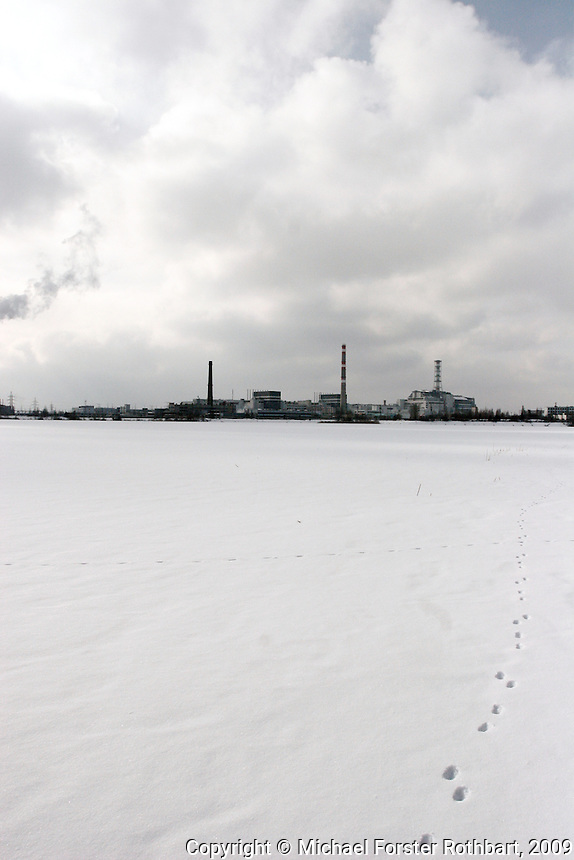 For workers arriving by train, this is the first view of the sprawling Chernobyl nuclear power plant, across the cooling pond. The plant&rsquo;s heating operation has the only active smokestack. At right is the hulking shelter object, which covers the ruined fourth-block reactor.<br /> ------------------- <br /> This photograph is part the book of Would You Stay?, by Michael Forster Rothbart, published by TED Books in 2013. The photos come from Forster Rothbart&rsquo;s two long-term documentary photography projects, After Chernobyl and After Fukushima.<br /> &copy; Michael Forster Rothbart 2007-2013.<br /> www.afterchernobyl.com<br /> www.mfrphoto.com &bull; 607-267-4893 &bull; 607-436-2856<br /> 34 Spruce St, Oneonta, NY 13820<br /> 86 Three Mile Pond Rd, Vassalboro, ME 04989<br /> info@mfrphoto.com<br /> Photo by: Michael Forster Rothbart<br /> Date:  2/2009    File#:  Canon 5D digital camera frame 52126