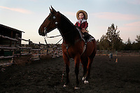 Josie Lauman, 2 1/2,  sits proudly and confidently on her mustang.  Her mother, Kitty Lauman, trains mustangs--as she says working with the horses, not against them.  They have a ranch in Prineville, OR.<br />