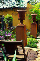Two rusted steel garden urns on pedestals in a small courtyard garden against walls painted a chalky ochre colour