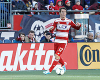 FC Dallas defender Zach Loyd (17) brings the ball forward and looks to pass..  In a Major League Soccer (MLS) match, FC Dallas (red) defeated the New England Revolution (blue), 1-0, at Gillette Stadium on March 30, 2013.