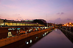 Early morning at Thewet Market, Bangkok, Thailand.  The canal that has fish and meat stalls on one side (left) and plants on the other (right).  The canal is filled with catfish.
