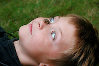 Photo of a boy Laying in the grass looking cross-eyed at a baby toad perched on his nose.