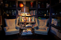 Two armchairs are placed either side of a a glass topped table with a lit lamp on top. Behind are books and pottery peices displayed on a shelving unit giving the room a cosy and compact feel.