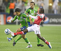 Seattle Sounders FC forward Fredy Montero, left, tries to escape from Portland Timbers midfielder Diego Chara during play at Qwest Field in Seattle Saturday May 14, 2011. The game ended 1-1 draw.