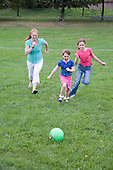 Mother and her daughters playing football in the park. MR