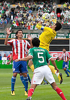 Justo Villar (1) makes the save between Aureliano Torres (17) and Ricardo Osorio (5). Mexico defeated Paraguay 3-1 at the Oakland Coliseum in Oakland, California on March 26th, 2011.