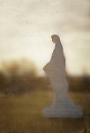 A religous statue stands in a field at sunset.