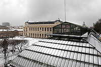 Plant History Glasshouse (formerly Australian Glasshouse), 1830s, Rohault de Fleury, Jardin des Plantes, Museum National d'Histoire Naturelle, Paris, France.  High angle view of rooftop covered in snow, with the Great Gallery of Evolution to the left and the Grande Mosquee de Paris (Great Mosque of Paris) in the background.