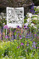 Garden Chair with Bird Ornamentation Detal in Flower garden in late spring, allium, Verbascum, Irises, salvia, spiky upright plants in romantic cottage garden style
