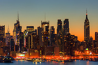The Manhattan skyline during morning twilight as viewed over the Hudson River looking east from New Jersey.  The eastern sky was accented with tinges of orange that began to show in the hour before sunrise.