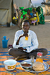 Abdel Karim Aboubakar, a Sudanese refugee, with his day's worth of food in the Breidjing Refugee Camp in eastern Chad near the Sudanese border. (From the book What I Eat; Around the World in 60 Diets.) The caloric value of his day's worth of food on a typical day in the month of November was 2300 kcals. He is 16 years of age; 5 feet 9.5 inches tall; and 110 pounds. He escaped over the border from the volatile Darfur region of Sudan into eastern Chad with his mother and siblings, just ahead of the Janjawiid militia that were burning villages of ethnically black African Sudanese. Like thousands of other refugees, they were accepted into the camp program administrated by the Office of the United Nations High Commissioner for Refugees (UNHCR). Their meals are markedly similar to those they ate in their home country, there's just less of it. They eat a grain porridge called aiysh, with a thin soup flavored with a dried vegetable or sometimes a small chunk of dried meat if Abdel Karim's mother has been able to work in a villager's field for a day or two. MODEL RELEASED.