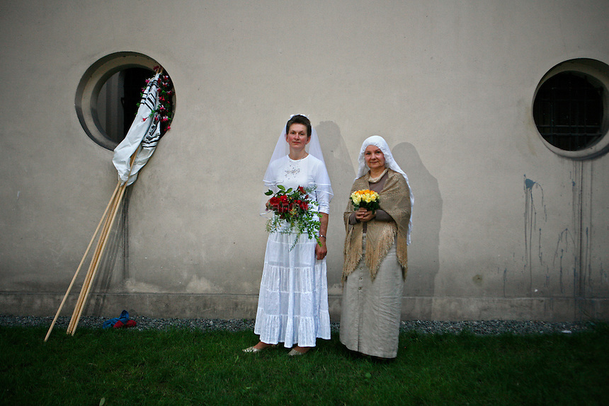 Two Polish converts to Judaism pose for a portrait after their consecutive weddings in the Kazimerz district of Krakow. <br /> <br /> Before the fall of communism in Poland, the former Jewish neighborhood of Kazimerz in Krakow was run down and dangerous to visit at night. Today, the area draws thousdands of tourists a year from around the world. The neighborhood was once a bustling center of Jewish life before it was wiped out during WWII. Jewish-themed restaurants and cafes serve traditional Jewish and Polish cuisine and restored synagogues contain exhibits detailing pre-war Jewish life in Poland. Some controversy exists over anti-Semitic paintings and woodwork in some gift shops and restaurants. Kazimerz is also the center of Krakow's night life, where tourists and students visit a variety of bars and night clubs. Klezmer music has seen a comeback as well, and musicians play concerts weekly. A short walk across the river to the south takes you to the former wartime ghetto and Oscar Schindler's factory, famously depicted in Steven Spielberg's film Schindler's List. The film was one of the determining factors in bringing attention to the Kazimerz district, resulting in massive restoration efforts.