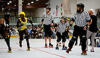 All of the inside referees watch as the jammer for the Crash Test Bunnies attempts to evade a blocker for the Psycho Ex Girlfriends.  From front to back the referees are: Al Capwn3d (front pack referee), Lollerskates (jammer referee), Cameltron (back pack referee), and Override (jammer referee; peeking out behind Lollerskates).  The penalty wrangler is visible to the right.  Portions of this image not central to the content have been digitally altered.