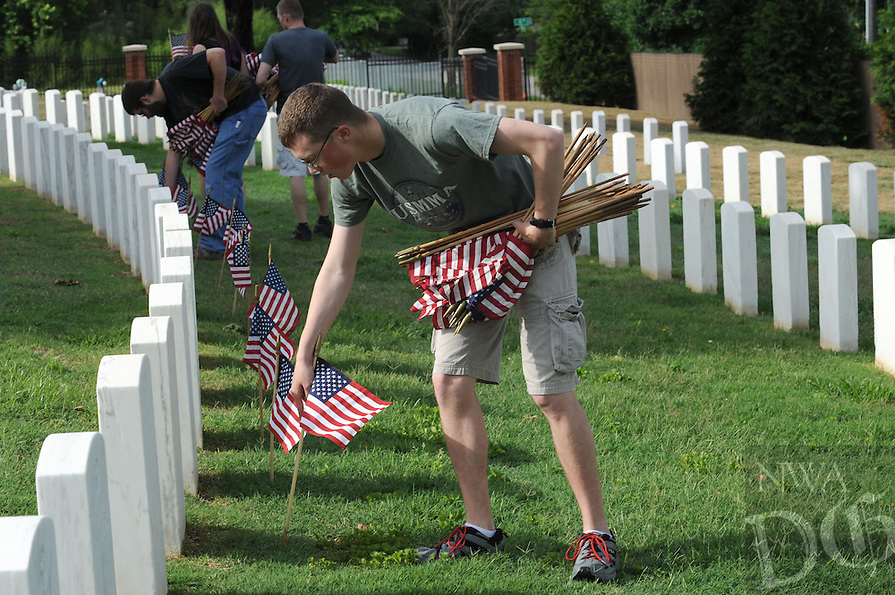 NWA Democrat-Gazette/ANDY SHUPE<br /> Austin Collins of Fayetteville places flags Saturday, May 28, 2016, along a row of grave markers at the Fayetteville National Cemetery. Volunteers placed flags in front of the approximately 8,700 grave markers at the facility ahead of the Memorial Day holiday. A service is planned for 10 a.m. Monday at the cemetery featuring Col. Bobbi Doorenbos, commander of Arkansas Air National Guard&rsquo;s 188th Wing.