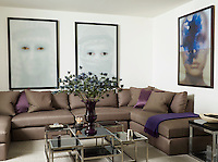 A custom-made sofa in a family room is covered in a glazed linen from Nicholas Haslam Ltd., the photographs are by Halim Al Karim. The cocktail table was found at Harrods, and the sisal rug is by Tim Page Carpets.