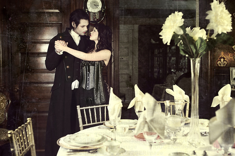 A young man and a young woman wearing dark goth clothing with a dining table in the foreground
