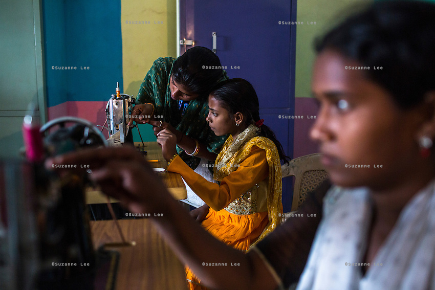 Students of the 'fashion design' tailoring course work with their sewing machines in the Guria Non-Formal Education center in the middle of the Shivdaspur red light district, Varanasi, Uttar Pradesh, India on 20 November 2013. These girls, daughters of women in prostitution, strive to break stigma and the cycle of prostitution by learning skills that will allow them to work in regular jobs.