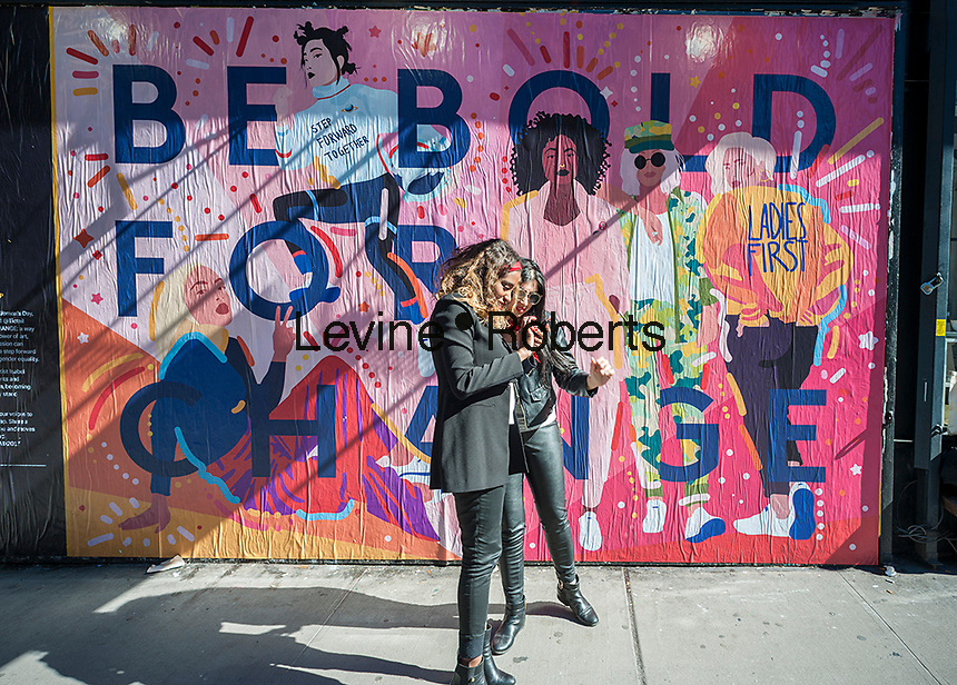"""Women admire their selfies in front of a """"Be Bold For Change"""" mural on the outside wall of the Tictail store in the Lower East Side neighborhood of New York on Wednesday, March 8, 2017. The mural was created by artist Isabel Castillo Guijarro specifically for the International Women's Day shopping event at the Tictail store. (© Richard B. Levine)"""