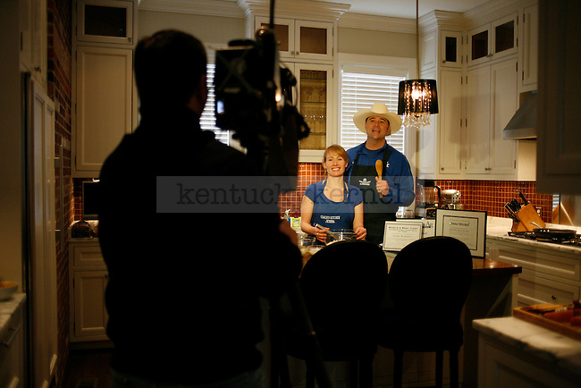 Coach Matthew Mitchell, right, stands with his wife, Jenna Mitchell, left, at the taping of Coach's Kitchen in Lexington, Ky., on Wednesday, February 27, 2013. Mitchell's cooking segment is unscripted. Photo by Tessa Lighty | Staff