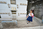 """Four-year old Salia Suleman walks through the Manila North Cemetery on her way to preschool. Hundreds of poor families live here, dwelling in and between the tombs and mausoleums of the city's wealthy. They are often discriminated against, and many of their children don't go to school because they're too hungry to study and they're often called """"vampires"""" by their classmates. With support from United Methodist Women, KKFI provides classroom education and meals to kids from the cemetery at a nearby United Methodist Church."""