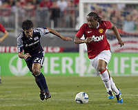 Manchester United FC forward Dimitar Berbatov (9) accelerates and New England Revolution midfielder Benny Feilhaber (22) defends. In a Herbalife World Football Challenge 2011 friendly match, Manchester United FC defeated the New England Revolution, 4-1, at Gillette Stadium on July 13, 2011.