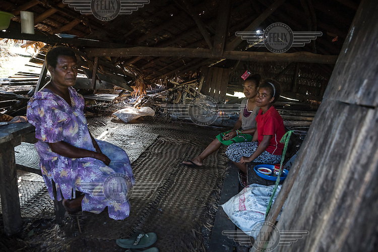 Total Sam (45) with her daughters Melina (19, left) and Sarina (14, right) inside their house, which was badly damaged by Cyclone Pam on 13 March 2015. SHe says: 'Our house wasn't strong enough to hold the strong wind. We still use the house, but it's very dangerous to sleep here, so we come here to cook only and we sleep outside.'