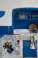 This simple kitchen has a marble sink set into a tiled work surface with an open shelf in the whitewashed wall painted a royal blue