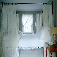 Sheer lace curtains and crisp white bedding have been combined with grey walls to create this subtly feminine bedroom