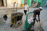Man cleaning a city street near Plaza Vieja, Havana, Cuba.