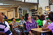 Customers share a light moment while looking at customer testimonials at Penang's famous Teo Chew Chendol restaurant in Georgetown of Penang, Malaysia. Photo: Sanjit Das/Panos