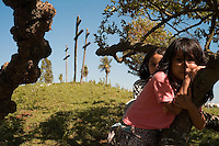 Daihina Servin (cq), 5, right, and Yanicia Montiel, 10, hang from tree branches near a small calvary hill that dates from a 17th-century mission in Santa Maria de Fé (acute accent on the e in Fe), Paraguay. Scores of Jesuit missions in the area where Paraguay, Argentina and Brazil meet were built in the 17th century and abandoned when the Jesuits were expelled in the 18th century. Ruins of some of these missions still haunt hilltops in the region. (Kevin Moloney for the New York Times)