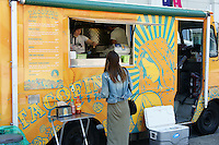 Young woman being served at a Mexican food truck in downtown Vancouver, British Columbia, Canada