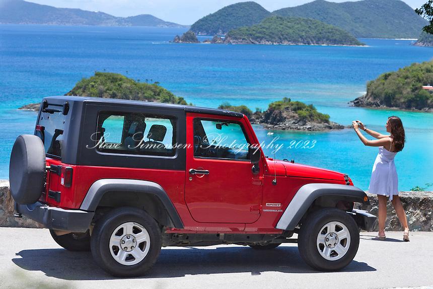 Tourist taking a picture near a red jeep<br /> Trunk Bay overlook<br /> Virgin Islands National Park<br /> St. John<br /> U.S. Virgin Islands