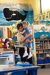 Berkeley CA  Preschool teacher being greeted by student in well-decorated acquatic-themed classroom.