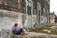 Young male worker sitting outside the main building at Hacienda Yaxcopoil, Yucatan, Mexico.