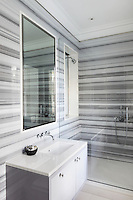 Striped, grey and white marble envelopes the walls of a minimal, contemporary bathroom