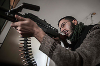 In this Monday, Dec. 10, 2012 photo, a Syrian rebel fighter watchs over the position of troops loyal to President Bashar al-Assad during clashes in Aleppo, Syria. (AP Photo/Narciso Contreras)