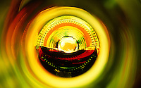 """Beauty at the Bottom: Red Wine 3""- This image is a photograph of a wine bottle shot right down the mouth of the bottle. A television provides the main light source."