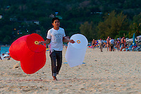 Thai boy selling sky lanterns on the beach at sunset, Phuket, Thailand