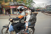 Vietnam. Hanoi. Rush hour traffic. Father, mother and son ride a scooter on the road, The young boy is wearing a mask on his mouth to protect him from the air pollution. 04.04.09 © 2009 Didier Ruef