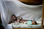 BUKAVU, DEMOCRATIC REPUBLIC OF CONGO - OCTOBER 29: Emiliana Azemahi, age 14, rests with her 10-month old baby boy Moises in the bed in her room on October 29, 2007 Bukavu, DRC. Emiliana was abducted and held for about 3 weeks in 2006. She was raped and abused for weeks by rebels before being released. She later became pregnant and gave birth to Moises in early January 2007. She now lives in a safe house in Panzi, outside Bukavu, DRC. The DRC conflict has seen an unprecedented high rate of rape and abuse of women. Done both by government soldiers and different rebel forces. (Photo by Per-Anders