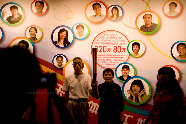 A couple poses with a mock up of the Olympic torch at the Coca-Cola building on the Olympic Green in Beijing, China on Thursday, August 21, 2008.  Kevin German